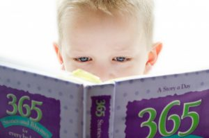 young child reading large book