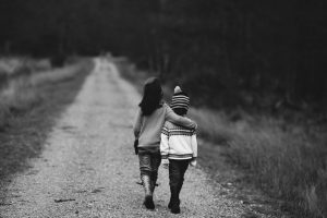 back and white photo of boy and girl walking down dirt road