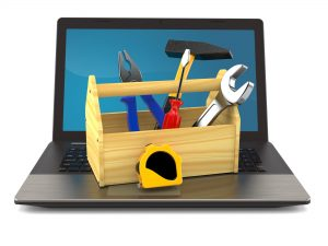 wooden toolbox with misc tools sitting on top of a laptop