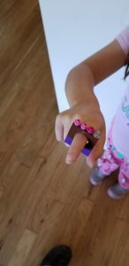 Girls hand wearing a ring made of legos