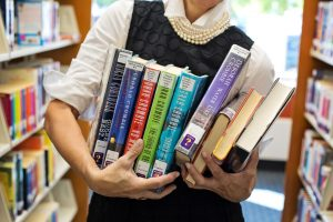 woman holding assorted library books